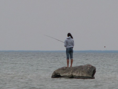 Girl Fishing From Rock